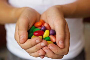 Caramelos de colores en las manos de niño