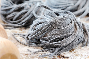 Homemade fresh black squid ink tagliolini pasta nests