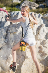 Rear view of blonde active woman climbing