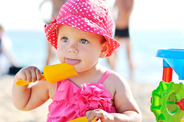 baby playing toys on beach