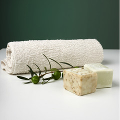 Handmade olive soap with olive branch and a towel.