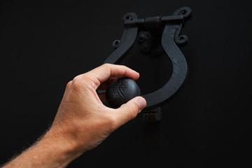 Male hand knocking old black metal door