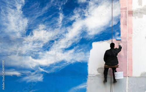 Painter paints bright blue sky on the urban wall