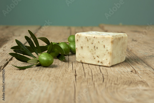 Handmade olive soap with olive branch on wooden table.