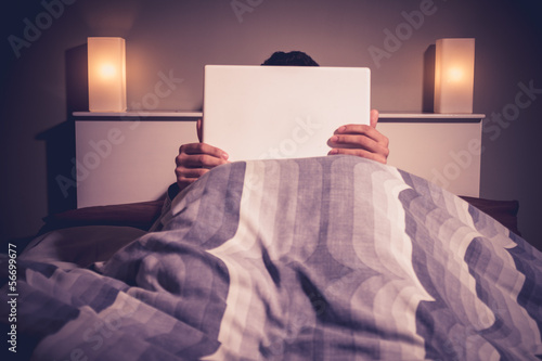 Man is sitting in bed behind his laptop