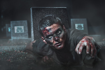 scary zombie crawls out of the grave