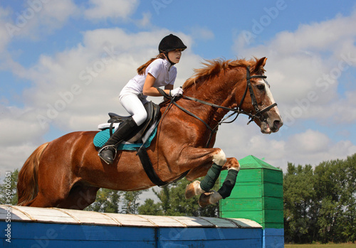 Young woman and her horse clear the wood wall obstacle