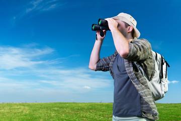 Explorer looking through binoculars outdoors