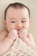 Teething Asian baby girl