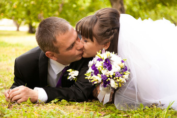 Married couple laying on grass in park and kissing