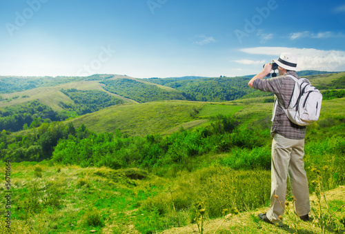 Explorer watching beautiful landscape through binoculars