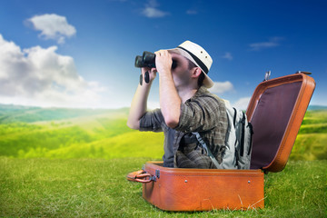 Traveling explorer observes nature from a luggage