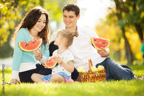 Happy family having a picnic in the autumn garden