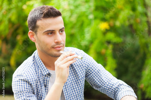 Man smoking an electronic cigarette in a park