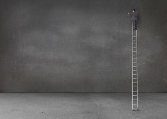 Businessman standing on a giant ladder in an empty room