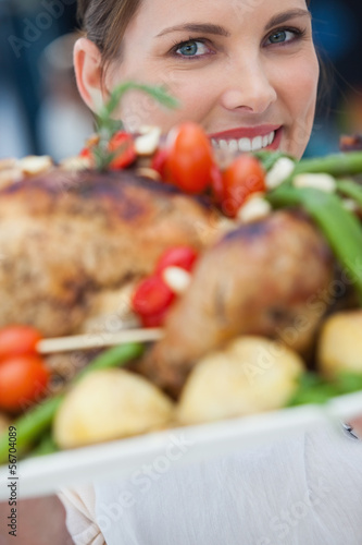 Pretty woman showing roast chicken