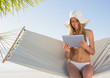 Cheerful blonde sitting on hammock using tablet pc