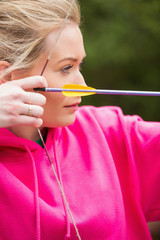 Focused blonde practicing archery