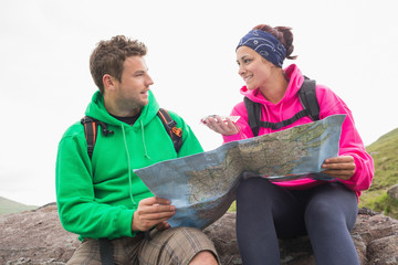 Couple using map and compass sitting on a rock