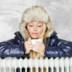 Winter lady with cap and radiator drinking hot tea