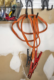 Old pair of jumper cables hanging on a garage wall
