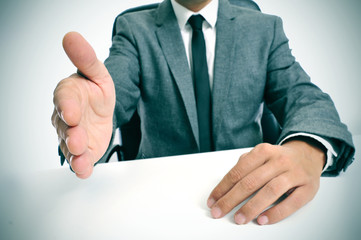 man in suit offering to shake hands