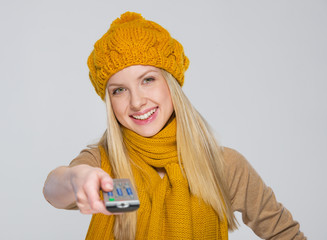 Happy girl in scarf and hat with tv remote control