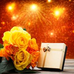Geschenk mit Rosen vor Feuerwerkshintergrund