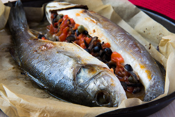 Grilled whole white fish, sea bass stuffed with tomato, olives