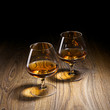 Two goblets of brandy warmed by the glow of the lights on wooden