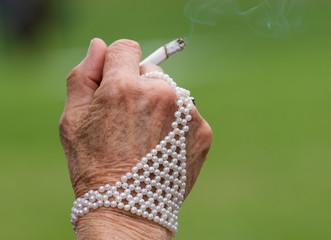 Older woman has a pearls jewellery on her hand