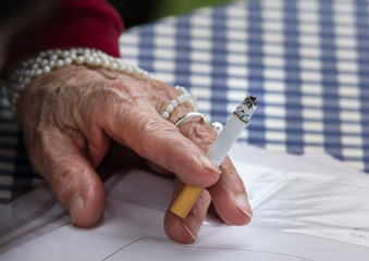 Older woman holds cigarette in her hand on table