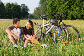 Young Couple Cycling In Meadow