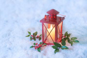 Rote Laterne mit Ilex im Schnee