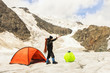 The climber costs on glacier near tent