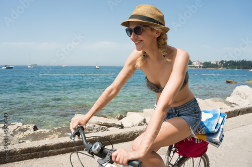 young woman cycling by the sea