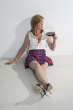 Woman partygoer drinking red wine from large glass