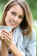 Beautiful smiling woman drinking hot drink in garden