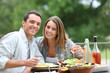 Cheerful couple having lunch in hotel garden