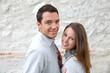 Cheerful couple standing in front of stone wall