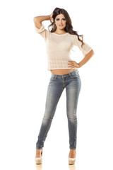 smiling young woman in jeans and blouse posing on white