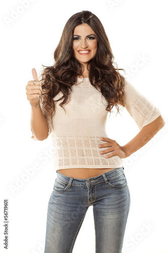 smiling young attractive woman in jeans showing thumbs up