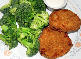 Crispy breaded chicken patties with broccoli and sauce
