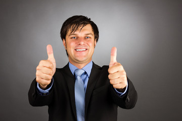 Happy young business man showing thumbs up gesture