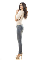 side view of young woman in jeans posing on white background