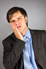 Portrait of a young businessman with toothache