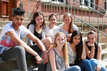 Gruppe Schüler sitzt auf einer Treppe