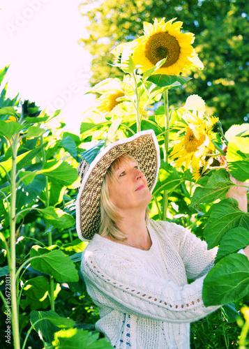 Frau im Spätsommer mit großen Sonnenblumen