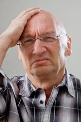 Mann mit Glatze hat Kopfschmerzen
