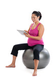 Pregnant woman on fitness ball doing exercise research on ipad